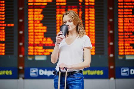 수하물과 커피를 들고 국제공항에 있는 젊은 여성이 비행 정보 디스플레이 근처로 이동합니다