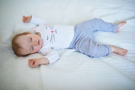 Adorable baby girl sleeping in crib. Small kid having day nap in parents bed Reklamní fotografie
