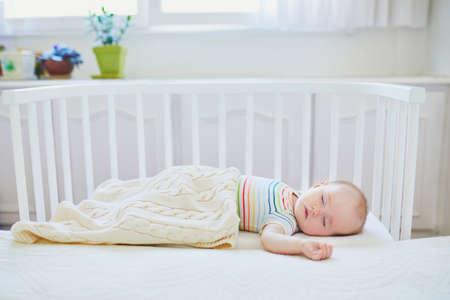 Entzückendes Baby, das im Beistellbett am Bett der Eltern schläft. Kleines Kind, das ein Tagesschläfchen im Kinderbett macht. Schlaftrainingskonzept. Kleinkind im sonnigen Kindergarten