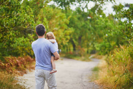 Father carrying his shild during walk in forest. Man with his adorable toddler daughter enjoying nature together