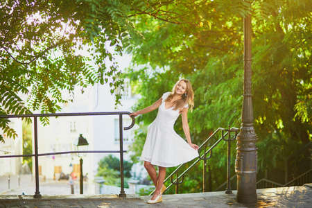 Beautiful young woman in white dress walking on famous Montmartre hill in Paris, France at early morning