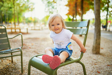 Happy little girl sitting on green metal chair in Luxembourg garden of Paris, France Stock fotó
