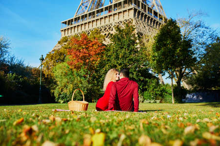 Romantic couple in love having picnic on the grass near the Eiffel tower on autumn day in Paris, France