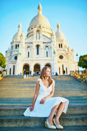 Beautiful young woman in white dress near Sacre-Coeur cathedral on famous Montmartre hill in Paris, France at early morning