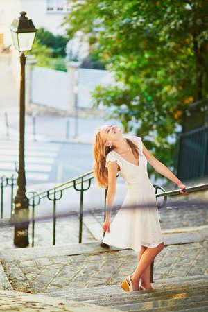 Belle jeune femme en robe blanche marchant sur la célèbre colline de Montmartre à Paris, France tôt le matin