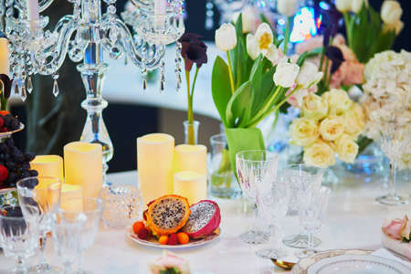 Beautiful table set with candles, fruits and flowers for a festive event, party or wedding reception
