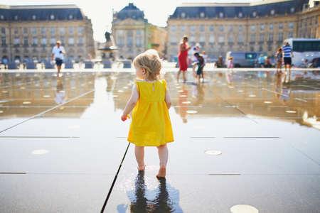 Adorable petite fille en robe jaune s'amusant célèbre fontaine d'eau extérieure (Miroir d'eau) à Bordeaux, France par une chaude journée d'été. Activités estivales pour les enfants Banque d'images