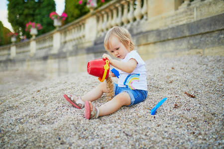 Little girl sitting on a large heap of stones and playing with pebbles in Luxembourg garden of Paris, France. Toddler playing with sand molds. Outdoor creative activities for kids