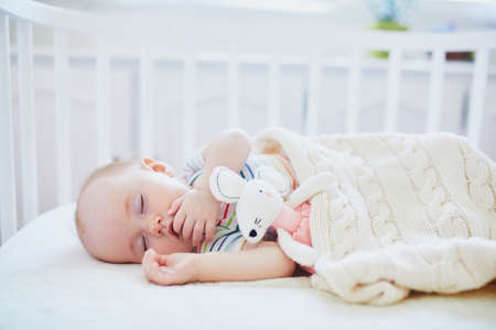 Adorable baby girl sleeping in co-sleeper crib attached to parents bed with stuffed toy. Little child having a day nap in cot. Sleep training concept. Infant kid in sunny nursery Stock Photo
