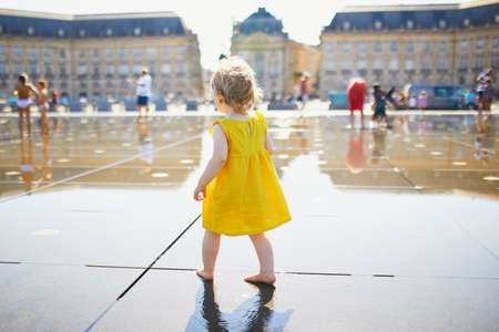 Adorable toddler girl in yellow dress having fun famous outdoor water fountain (Miroir deau) in Bordeaux, France on a hot summer day. Summer activities for kids