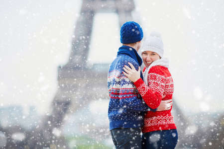 Happy couple near the Eiffel tower on a winter day under the falling snow. Trip to Paris during season holidays Zdjęcie Seryjne