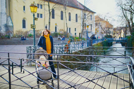 Happy young woman with her little baby girl in stroller. Mother walking with daughter in alpine town of Annecy, France Stock Photo - 131686003