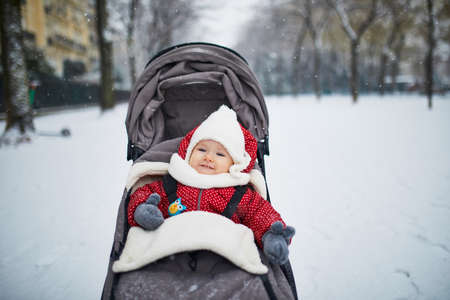 Happy smiling baby girl in stroller in Paris day with heavy snow. Little kid enjoying the very first snow. Unusual weather conditions in Franc