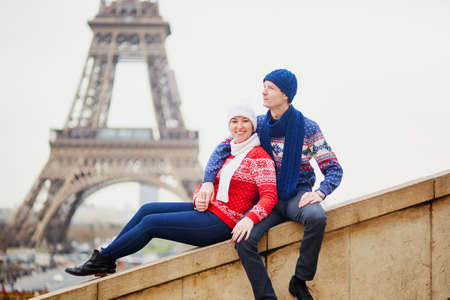 Happy couple near the Eiffel tower on a winter day. Trip to Paris during season holidays