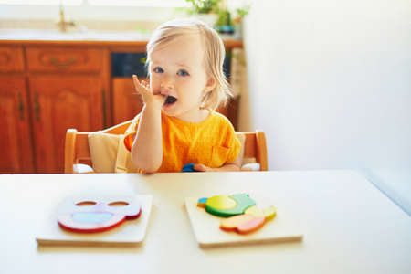 Adorable toddler girl doing wooden puzzle. Kid learning to solve problems and developing cognitive skills