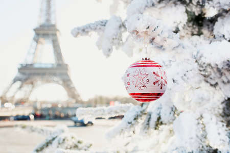 Christmas tree covered with snow and decorated with red ball near the Eiffel tower in Paris, France Zdjęcie Seryjne