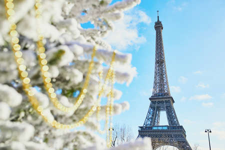 Christmas tree covered with snow and decorated with beads near the Eiffel tower in Paris. Celebrating seasonal holidays in France