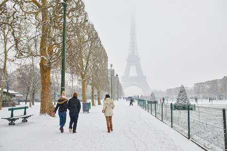 Scenic view to the Eiffel tower on a day with heavy snow. People walking with umbrellas on a snowy day in Paris. Unusual weather conditions in Paris