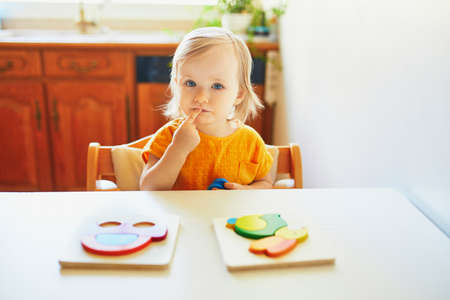 Adorable toddler girl doing wooden puzzle, looking confused, not sure what to do next. Kid learning to solve problems and developing cognitive skills Banco de Imagens