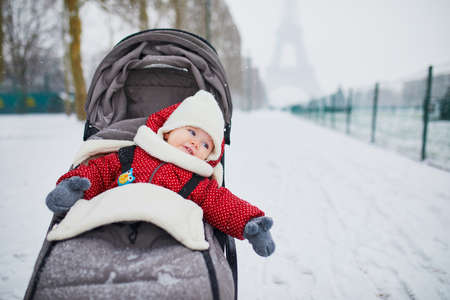 Happy smiling baby girl in stroller near the Eiffel tower on a day with heavy snow. Little kid enjoying the very first snow. Unusual weather conditions in Paris