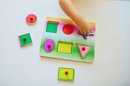 Toddler girl or boy doing wooden puzzle. Child learning geometric shapes. Kid learning to solve problems and developing cognitive skills