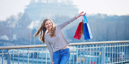 Beautiful young girl with shopping bags near the Eiffel tower. Shopping tourism in Paris concept