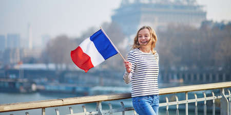 Beautiful young girl with French national tricolor flag near the Eiffel tower Banco de Imagens