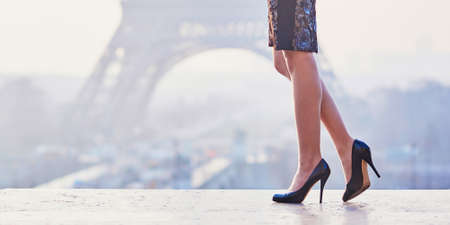 Femme portant des chaussures à talons hauts et marchant près de la tour Eiffel au petit matin à Paris, gros plan des jambes Banque d'images