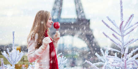 Girl with caramel apple on a Parisian Christmas market during snowfall near white snowy Christmas trees and with the Eiffel tower in the background Banque d'images