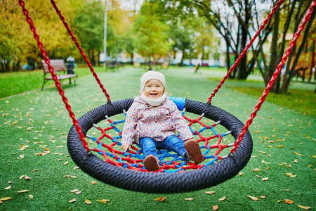 Adorable little girl on the playground. Toddler having fun on basket swing on a fall day. Outdoor activities for small kids