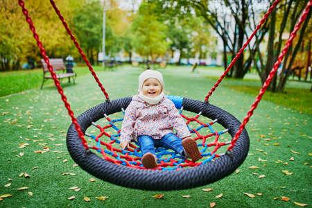 Adorable niña en el patio de recreo. Niño que se divierte en el columpio de la canasta en un día de otoño. Actividades al aire libre para niños pequeños Foto de archivo