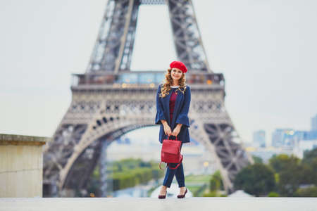 Young woman with long blond curly hair in Paris, France. Beautiful tourist in red beret near the Eiffel tower Standard-Bild - 132470270