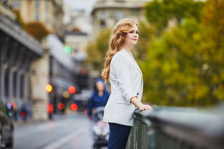 Young woman with long blond curly hair in Paris, France. Beautiful tourist in white jacket on Bir-Hakeim bridge Standard-Bild - 132470278