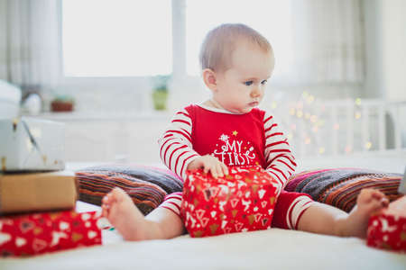 Happy little baby girl wearing pyjamas opening Christmas presents on her very first Christmas. Celebrating Xmas with kids at home