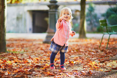 Adorable cheerful toddler girl running in Tuileries garden in Paris, France. Happy child enjoying warm and sunny fall day. Outdoor autumn activities for kids Standard-Bild - 132470275