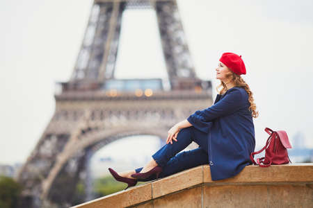 Young woman with long blond curly hair in Paris, France. Beautiful tourist in red beret near the Eiffel tower Standard-Bild - 132470281