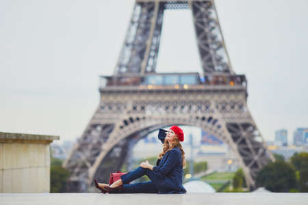 Young woman with long blond curly hair in Paris, France. Beautiful tourist in red beret near the Eiffel tower Standard-Bild - 132470282
