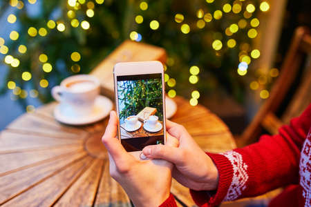 Woman taking photo of her coffee cup and Christmas present in cafe decorated for seasonal holidays