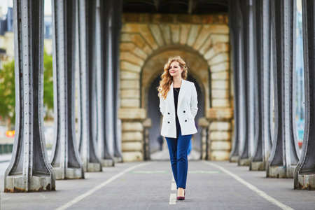 Young woman with long blond curly hair in Paris, France. Beautiful tourist in white jacket on Bir-Hakeim bridge Standard-Bild - 132470287