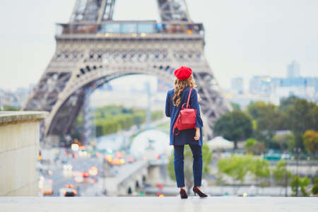 Young woman with long blond curly hair in Paris, France. Beautiful tourist in red beret near the Eiffel tower Standard-Bild - 132470294