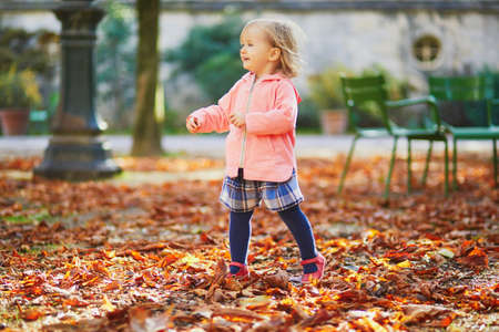 Adorable cheerful toddler girl running in Tuileries garden in Paris, France. Happy child enjoying warm and sunny fall day. Outdoor autumn activities for kids Standard-Bild - 132470295