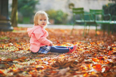 Adorable toddler girl sitting on the ground in Tuileries garden in Paris, France. Happy child enjoying warm and sunny fall day. Outdoor autumn activities for kids Standard-Bild - 132470297