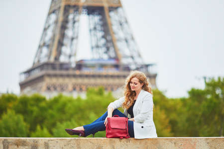 Young woman with long blond curly hair in Paris, France. Beautiful tourist in white jacket near the Eiffel tower, on the Seine embankment Standard-Bild - 132470296