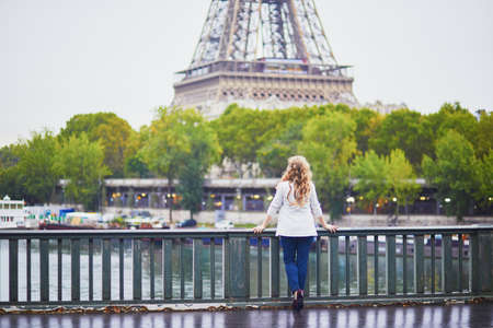 Young woman with long blond curly hair in Paris, France. Beautiful tourist in white jacket near the Eiffel tower, on the Seine embankment Standard-Bild - 132470343