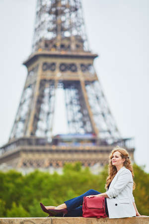 Young woman with long blond curly hair in Paris, France. Beautiful tourist in white jacket near the Eiffel tower, on the Seine embankment Standard-Bild - 132470348