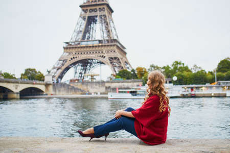Young woman with long blond curly hair in Paris, France. Beautiful tourist in red coat near the Eiffel tower, on the Seine embankment Standard-Bild - 132470411