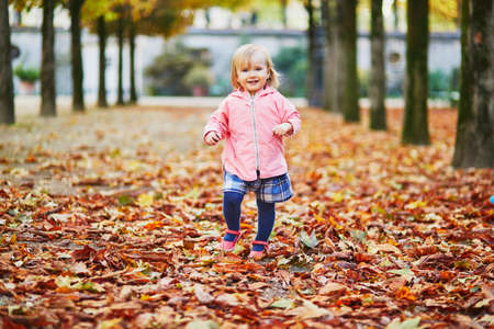 Adorable cheerful toddler girl running in Tuileries garden in Paris, France. Happy child enjoying warm and sunny fall day. Outdoor autumn activities for kids