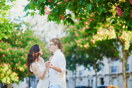 Happy romantic couple in Paris, hugging under pink chestnuts in full bloom. Tourists spending their vacation in France Standard-Bild - 132470417