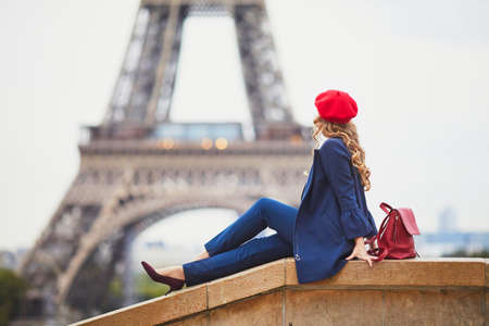Young woman with long blond curly hair in Paris, France. Beautiful tourist in red beret near the Eiffel tower Standard-Bild - 132470419