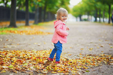 Adorable cheerful toddler girl running in park in Paris, France. Happy child enjoying warm and sunny fall day. Outdoor autumn activities for kids Standard-Bild - 132470420